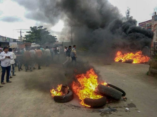 Smoke billows from a burning tyre during a protest rally demanding reservation for Marathis, at Neknoor village in Beed district on Tuesday, July 24, 2018. Maratha outfits have called for a bandh in Maharashtra a day after of a protestor demanding reservation for the community jumped off a bridge over Godavari river and died, in Aurangabad. PTI Photo
