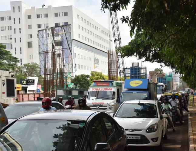 An ambulance is stuck in a traffic jam on Bannerghatta Road where metro work is underway. DH Photo/Janardhan B K