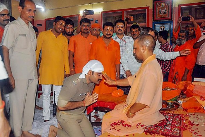 A police officer in uniform kneels down at the feet of Uttar Pradesh Chief Minister Yogi Adityanath, on the occasion of Guru Purnima at the Gorakhnath temple, in Gorakhnath on Friday. Adityanath is also head priest of the Gorakhnath Math. PTI
