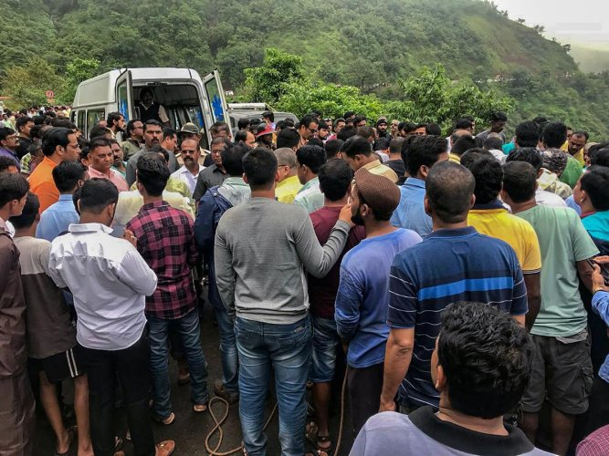 Tragedy: People gather at the site where a bus fell into a gorge in the Konkan region, killing 33 on Saturday. PTI