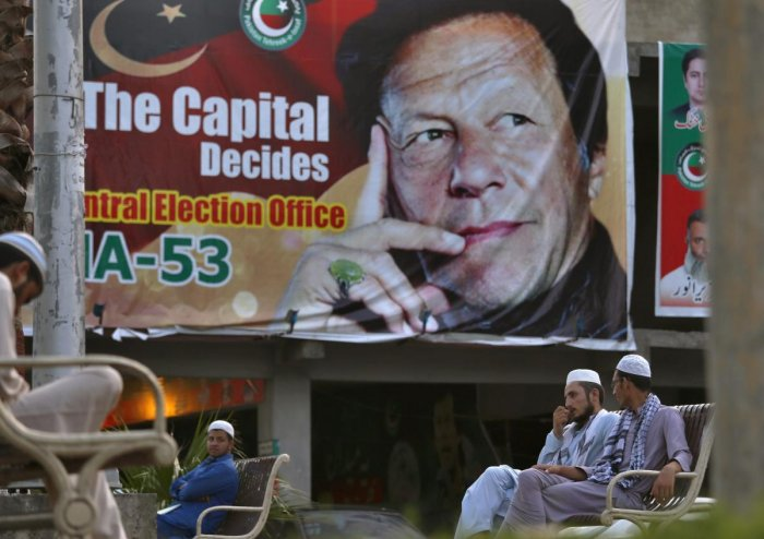 Pakistanis chat while they sit on a bench next to a big poster of Imran Khan, head of Pakistan Tehreek-e-Insaf party, at a market in Islamabad, Pakistan. AP/PTI file photo