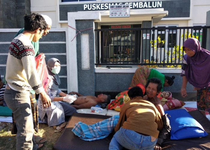 An Indonesia paramedic gives treatment to injured people outside of a hospital after an earthquake hit Sembalun Selong village in Lombok Timur, Indonesia. Reuters