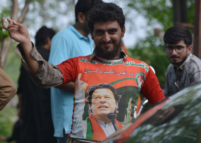 A supporter of Pakistan's cricketer-turned politician Imran Khan, and head of the Pakistan Tehreek-e-Insaf (Movement for Justice) party, gestures as he wears a t-shirt featuring an image of Khan's near his residence in Islamabad on July 26, 2018, a day af