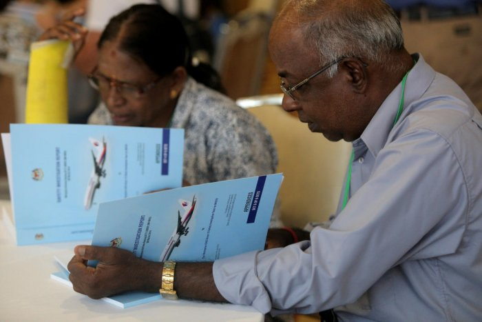 Family members read MH370 briefing reports before a closed door meeting in Putrajaya, Malaysia, on Monday. Reuters