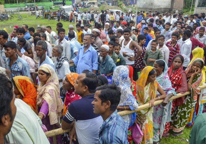 People wait to check their names on the final draft of the state's National Register of Citizens after it was released, at an NRC Seva Kendra in Tezpur on Monday, July 30, 2018. (PTI Photo)