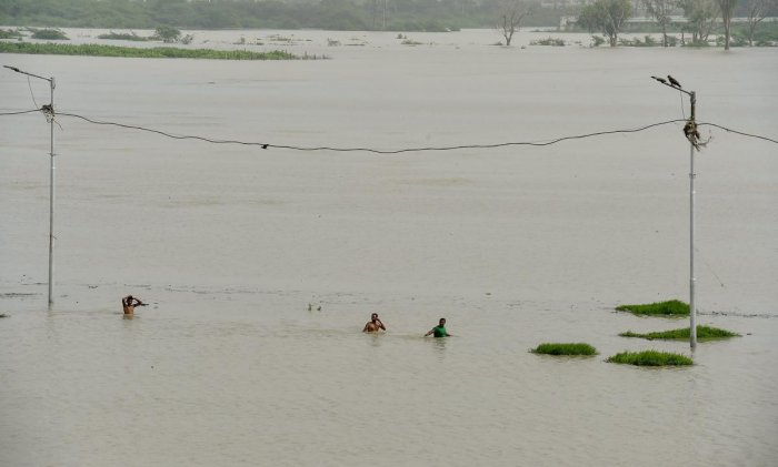 People make way through the flood waters at Usmanpur near the banks of Yamuna river, in New Delhi on Wednesday. (PTI Photo)