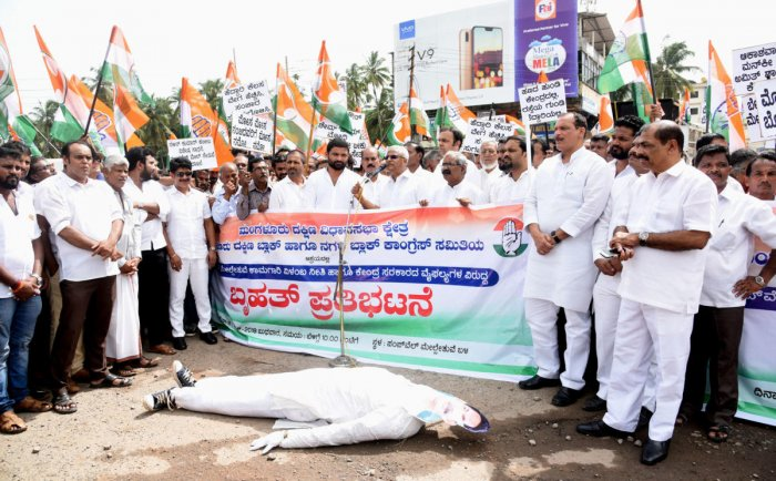 Congress workers stage a protest at Pumpwell Circle in Mangaluru on Wednesday against the delay in the work of flyovers and poor condition of the national highway.