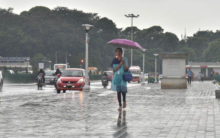 A woman walks with a umbrella during a sudden downpour near Vidhana Soudha, in Bengaluru. (DH File Photo/Janardhan B K)