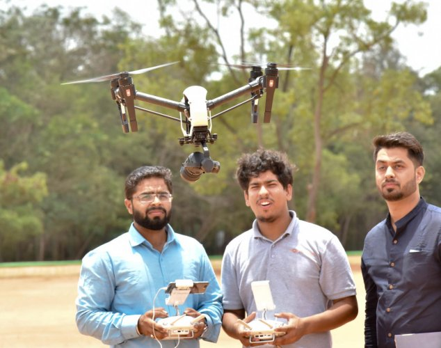 Volunteers operate a drone camera at the launch of Drone applications for Agriculture activities at GKVK in Bengaluru on Thursday. DH Photo/Janardhan B K