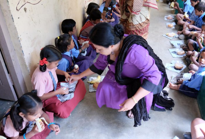 Sarala Menon, former president, Inner Wheel Club of Bangalore IT Corridor (IWCBITC), distributing food to children of the Government Lower Primary School at Pattandur Agrahara, Whitefield, on Thursday. DH Photo/Grace Hauck