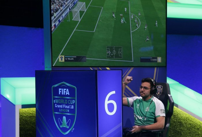 MAKING STRIDES Players compete on game consoles in the group stages of the FIFA eWorld Cup Grand Final in London. AFP