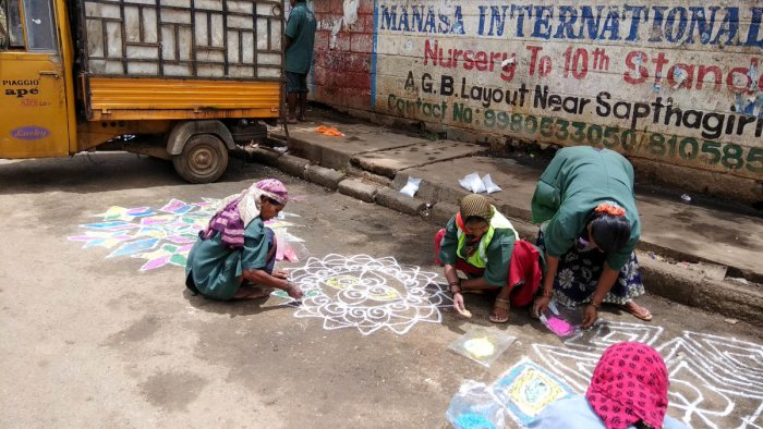 Municipal workers create rangoli artworks on a garbage black spot in Defence Colony near Bagalagunte, Hesaraghatta Main Road, on Friday. DH PHOTO/B H Shivakumar
