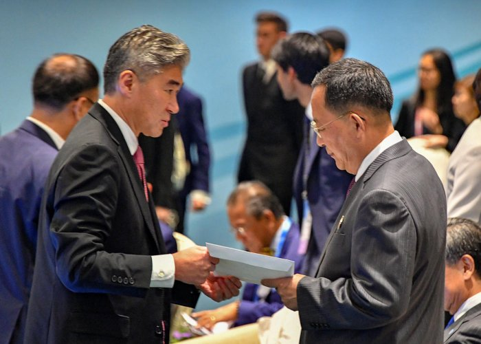 North Korea's Foreign Minister Ri Yong Ho is handed U.S. President Donald Trump's reply to North Korean leader Kim Jong Un's letter, by a member of the U.S. delegation at the ASEAN meeting in Singapore August 4, 2018. U.S. Department of State Handout via