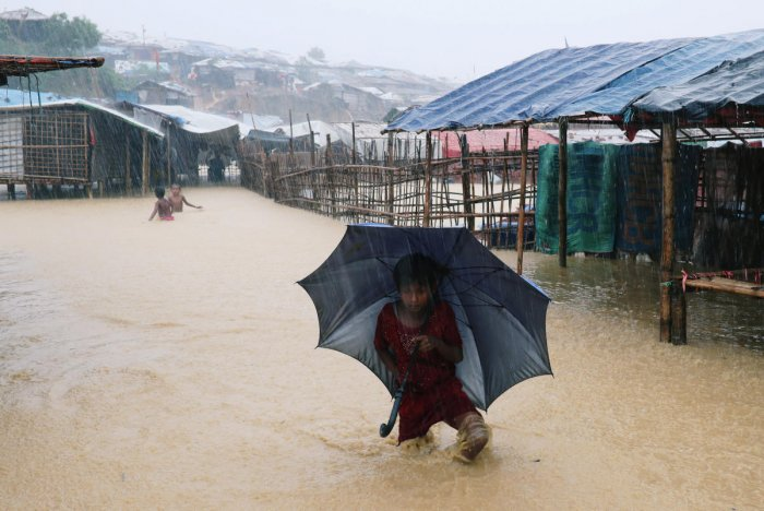 A Rohingya refugee girl walks along the water with umbrella as parts of the Kutupalong camp is flooded during heavy rain in Cox's Bazar, Bangladesh. (Reuters File Photo)