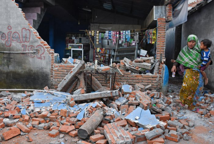 A woman walks past debris from a collapsed wall following a strong earthquake in Lendang Bajur Hamlet, Lombok island, indonesia August 6, 2018 in this photo taken by Antara Foto. Antara Foto/Ahmad Subaidi/ via REUTERS.