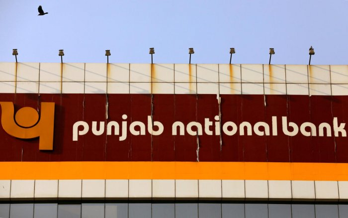 FILE PHOTO: A bird flies past the logo of Punjab National Bank installed on the facade of its office in Mumbai, India, February 21, 2018. REUTERS/Danish Siddiqui/File photo GLOBAL BUSINESS WEEK AHEAD