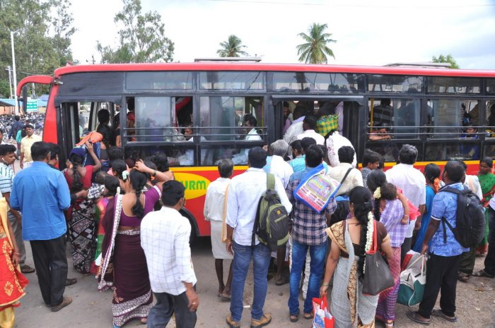 People board a city bus in Hosapete as private vehicles.