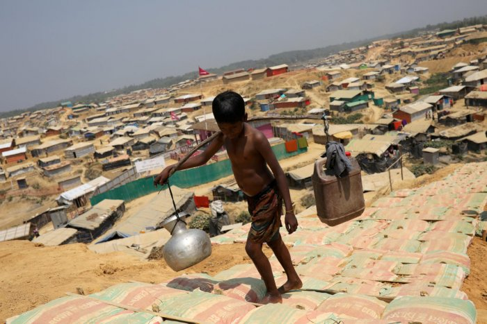 FILE PHOTO: A Rohingya refugee boy carries water in the Kutupalong refugee camp, in Cox's Bazar, Bangladesh March 22, 2018. REUTERS/Mohammad Ponir Hossain/File Photo