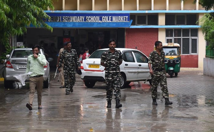 Indian security forces walk inside the government school where a seven years old girl student was sexually assaulted, in New Delhi on August 10, 2018. - Scores of angry parents protested outside a government-run school in New Delhi on August 10 after a se