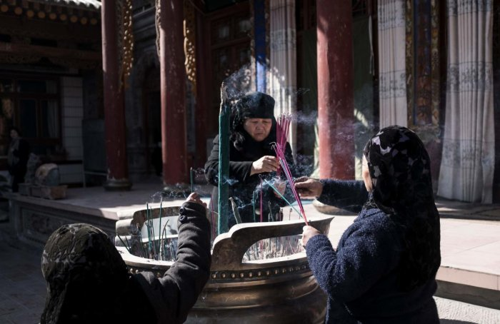 Ethnic Hui Muslim women pray in a courtyard at a religious site in Linxia, China's Gansu province on March 2, 2018. AFP