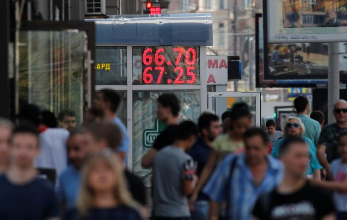 Pedestrians walk by an electronic board showing currency exchange rates of the US dollar against Russian rouble in Moscow on August 10, 2018. Reuters