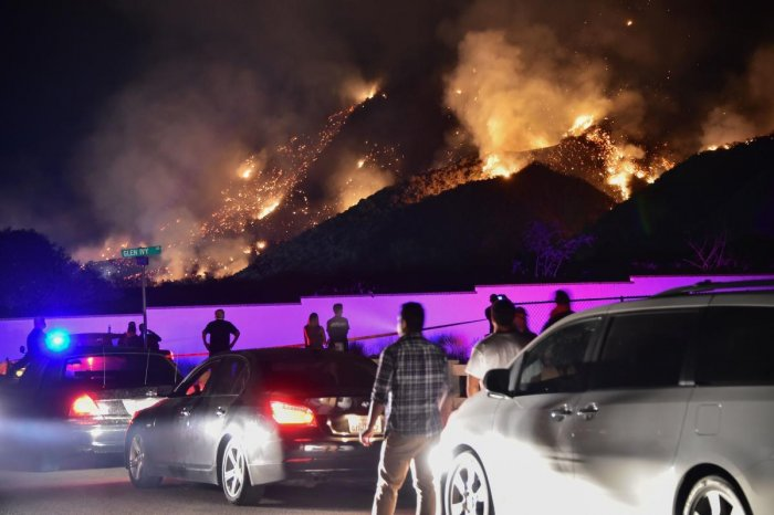 People watch flames from the 'Holy Fire' outside Glen Ivy Hot Springs in Corona, California, southeast of Los Angeles, on August 10, 2018. AFP