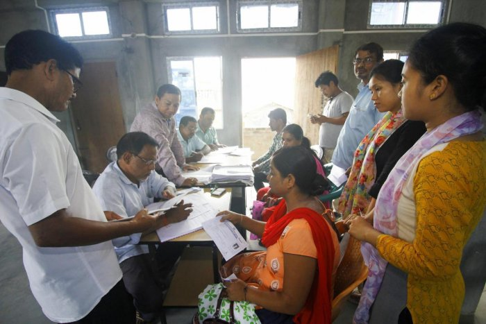 People whose names were missing in the final draft of National Register of Citizenship (NRC) published on 30th July 2018, filling new enrollment forms at an NRC Seva Kendra, in Guwahati on Saturday, Aug 11, 2018. (PTI Photo)