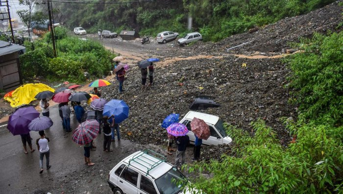 People try to retrieve vehicles from under the debris of a landslide following heavy rainfall in Shimla on Monday. (PTI Photo)