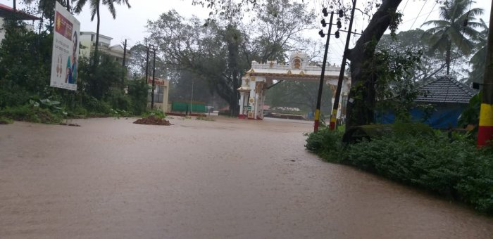 Water from the Kumaradhara river has inundated the road leading to the Kukke Subrahmanya Temple. (DH Photo)
