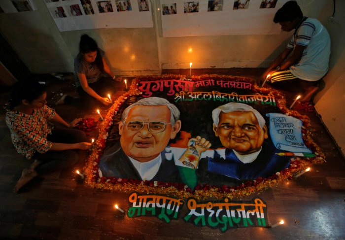 Students place candles around a painting featuring India's former prime minister Atal Bihari Vajpayee to pay him homage in Mumbai, India, August 16, 2018. (REUTERS)
