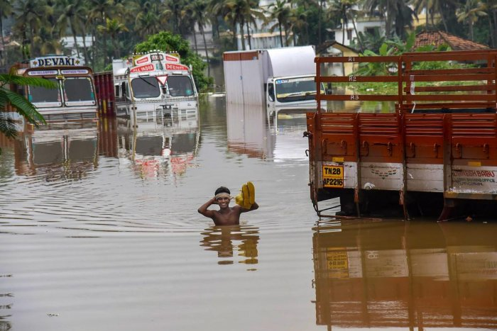 A person stands near submerged trucks on a waterlogged street at a flood-affected region following heavy monsoon rainfall, in Kochi on Thursday. PTI