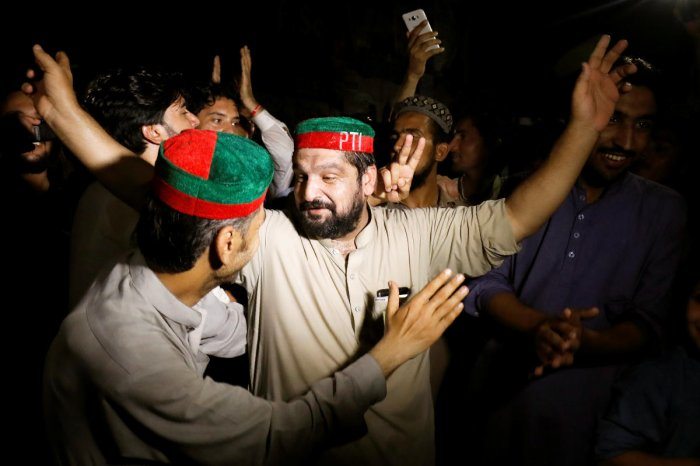 Supporters of Imran Khan, chairman of Pakistan Tehreek-e-Insaf (PTI) gesture to celebrate after Khan was elected as Prime Minister, in Peshawar, Pakistan August 17, 2018. (Reuters Photo)