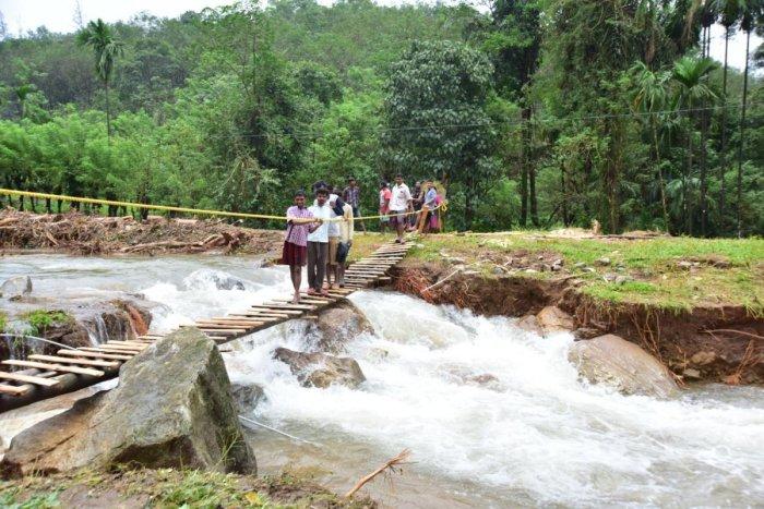 Labourers cross a stream on a makeshift bridge constructed at Kadamakallu Gudda in Kalmakaru, Dakshina Kannada district. DH PHOTO/Govindraj Javali
