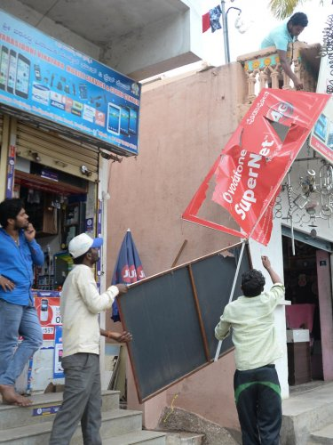 BBMP workers remove flex boards on Kodigehalli Main Road on Monday. DH PHOTO