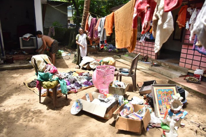 The family dries out clothes and other things outside their house after flood water receded at Purathuru in Kerala on Tuesday. DH Photo by Janardhan B K