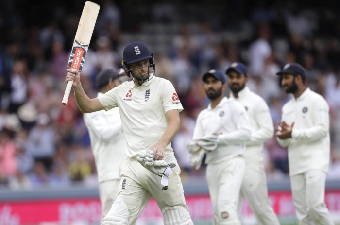 England's Chris Woakes is applauded by the Indian team as he leaves the pitch on 120 not out after bad light stopped play, during the third day of the second test match between England and India at Lord's cricket ground in London.