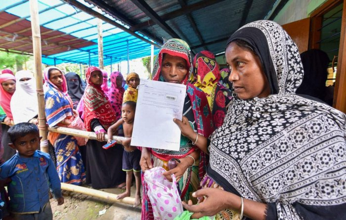 People wait to check their names on the final draft of the state's National Register of Citizens after it was released, at an NRC Seva Kendra in Nagaon. PTi
