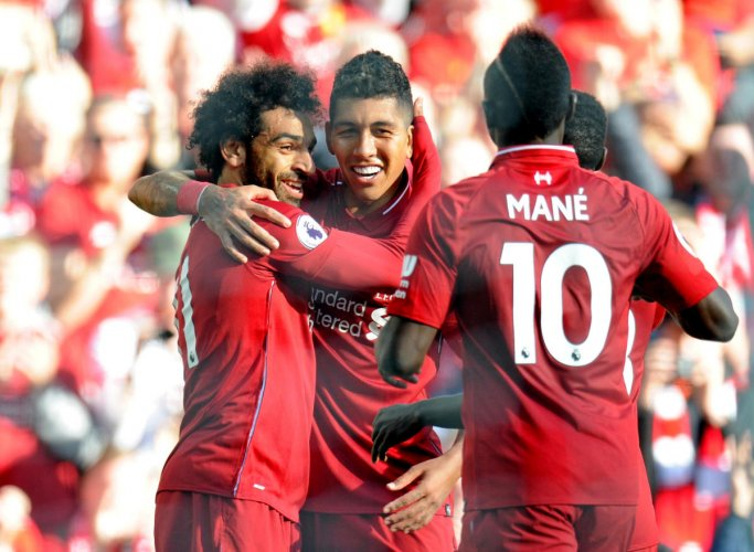 Liverpool's Mohamed Salah (left) celebrates with Roberto Firmino (centre) after scoring against Brighton on Saturday. REUTERS