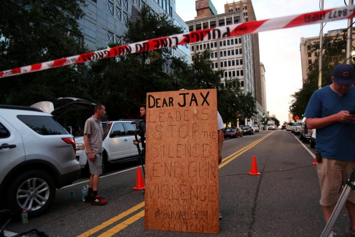 A man holds a sign in support of gun control outside of The Jacksonville Landing after a shooting in Jacksonville, Florida August 26, 2018. (REUTERS)