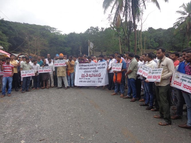 Villagers stage a protest demanding to allow light vehicles on Shiradi Ghat, at Gundya on Monday.