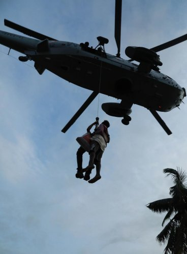A man being airlifted by Navy personnel during a rescue operation at a flooded area in Paravoor near Kochi, Kerala. AFP