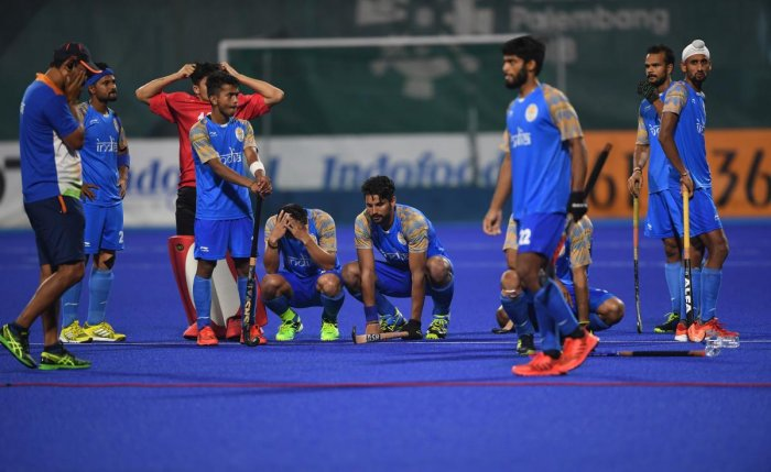 PICTURE SAYS IT ALL: Indian hockey team players and coach Harendra Singh (left) wear a dejected look after their semifinal loss to Malaysia in Jakarta on Thursday. AFP