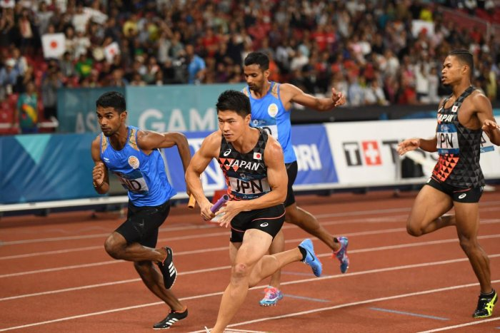 Japanese (front) and Indian athletes compete in the final of the men's 4x400m relay athletics event during the 2018 Asian Games in Jakarta on August 30, 2018. (Photo by Anthony WALLACE / AFP)