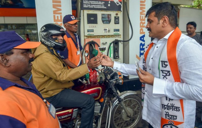 A Nationalist Congress Party (NCP) worker gives away a lotus motif to a motorcyclist at a petrol pump during a protest against the fuel price hike, in Mumbai on Tuesday, August 28, 2018. (PTI Photo/Shashank Parade)