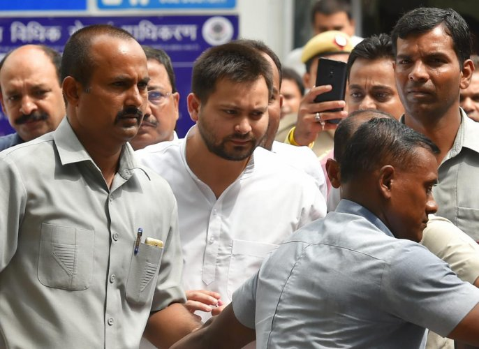 Tejashwi Prasad Yadav (C) son of former Bihar chief minister Lalu Prasad Yadav, comes out of Patiala House court after appearing before a special court in the (IRCTC) tender scam case, in New Delhi on Friday. PTI