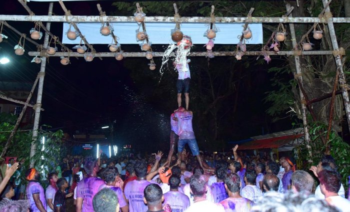 Youth form a pyramid and burst the pots containing curd, during Mosaru Kudike celebrations at Attavar in Mangaluru on Monday.