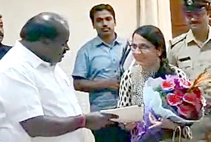 Chief Minister H D Kumaraswamy gives the flat documents to Vandana Kukreja in Bengaluru on Tuesday.