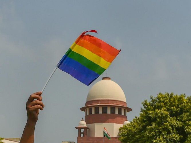 An activist waves a rainbow flag (LGBT pride flag) after the Supreme Court verdict which decriminalises consensual gay sex, outside the Supreme Court in New Delhi, Thursday, Sept 6, 2018. PTI Photo