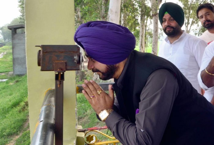 Punjab Local Bodies Minister Navjot Singh Sidhu pay obeisance while seeing Gurdwara Kartarpur Sahib, located in Pakistan, through a binocular from the Indo-Pak border in Gurdaspur district on Saturday, August 25, 2018. (PTI Photo)