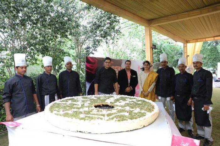 Adjudicator Shantanu Chauhan (center) and Divolka Jain with Gyanjee caterers team and the record making ghewar. (DH Photo/Tabeenah Anjum)